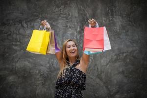 portret van een jonge gelukkig lachende vrouw met boodschappentassen