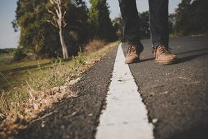 close-up van jonge toeristische man lopen op een landelijke weg foto