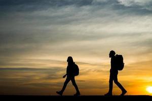 silhouetten van twee wandelaars met rugzakken die van de zonsondergang genieten foto