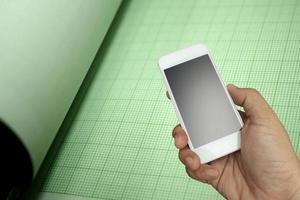 hand met de smartphone op groene grafiek foto