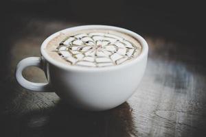 een kopje koffie op een houten tafel foto
