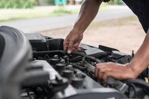 man die de motor van een auto controleert