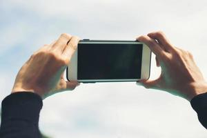 vrouwelijke handen nemen foto met een smartphone, uitzicht op de blauwe lucht en de wolk