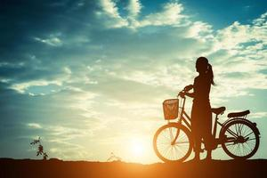 silhouet van een vrouw met een fiets en een mooie hemel foto