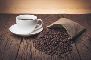 koffiekopje met koffiebonen op een houten tafel