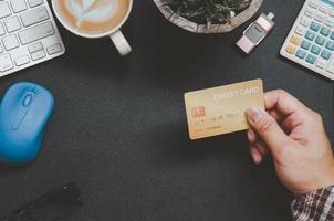 bovenaanzicht van iemand met een creditcard op een bureau