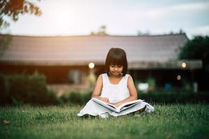 meisje dat een boek in haar huistuin buiten leest foto