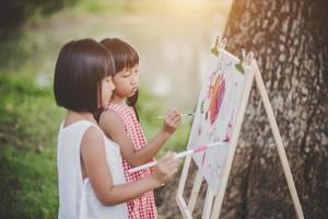 twee kleine meisjesschilders die kunst in het park trekken foto