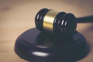 close-up van de hamer van een rechter op een houten achtergrond foto