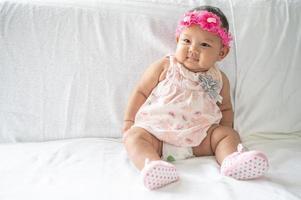 een baby die leert zitten op een wit bed