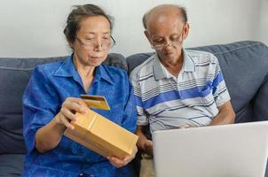 twee ouderen die online winkelen