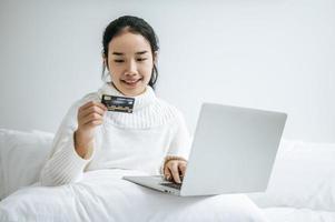 jonge vrouw die op laptop winkelt en een creditcard houdt foto