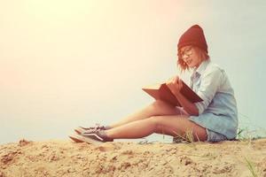 mooie jonge vrouw die een boek leest op het strand