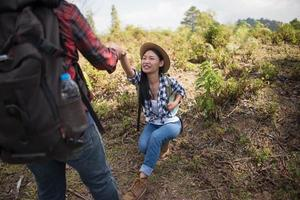 jong koppel wandelen met rugzakken in een bos foto