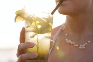vrouw genieten van een tropische mojito-cocktail foto