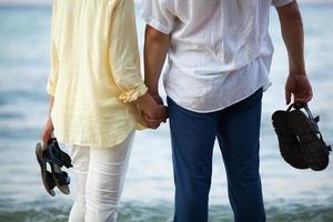 paar hand in hand aan de kust foto