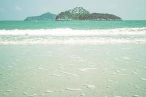 blauwe oceaangolf op zandstrand in thailand foto