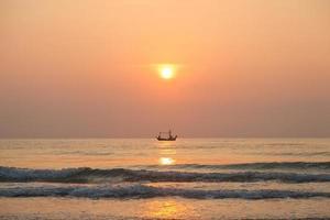 vissersboot op zee bij zonsopgang