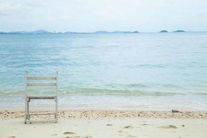 witte houten stoel aan zee foto