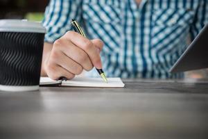 close-up van hand schrijven in notitieblok met pen foto