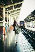 jonge hipster vrouw te wachten op het perron van het station met rugzak foto