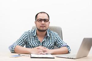 portret van een zakenman achter tafel geïsoleerd op een witte achtergrond foto