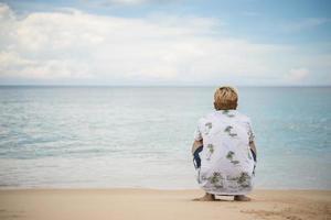 jonge hipster man ontspannen zittend op zee strand