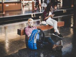 jonge hipster paar zittend op een houten bankje op het treinstation foto