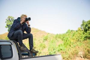 jonge fotograaf zittend op zijn pick-up truck fotograferen van een berg