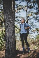 jonge vrouw reist met een rugzak in de natuur foto