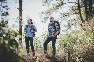 jong avontuurpaar dat naar een berg wandelt foto