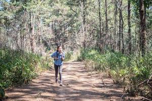 toerist die met rugzak door bos loopt foto