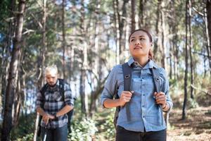 wandelen paar backpacken in het dennenbos foto