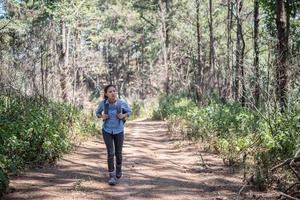 toerist die met rugzak door het bos loopt foto