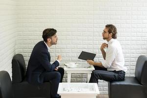 jonge zakenman in gesprek met collega in een moderne zakenlounge foto