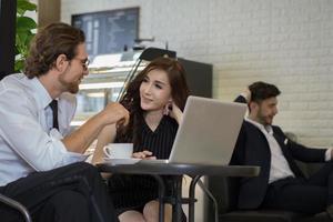 gelukkige collega's ontmoeten elkaar in café die op laptop werkt foto
