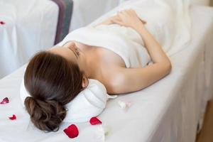 mooie lachende vrouw met bloemen rusten in de spa voor massage foto
