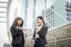 twee zakenvrouwen staan en bespreken hun werk voor het kantoor foto