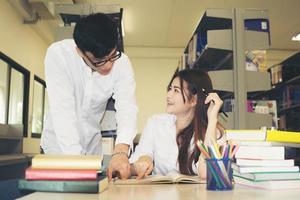 jonge Aziatische studenten in de bibliotheek die samen een boek lezen foto