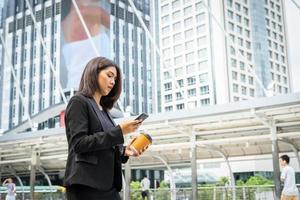 zakenvrouw met behulp van telefoon met koffie lopen op straat foto