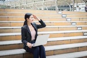 zakenvrouw met behulp van laptop zittend op trappen foto
