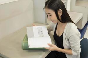 jonge Aziatische student bij de bibliotheek die een boek leest foto