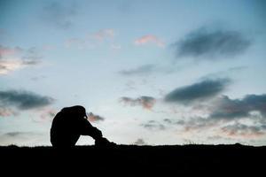 silhouet van triest vrouw hoofd op knieën bij zonsondergang foto