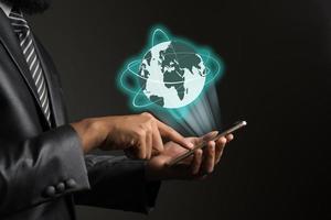 zakenman met smartphone en wereldwijd netwerk grafisch op scherminterface foto