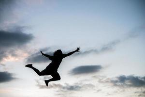 gelukkige jonge vrouw springen tegen de prachtige zonsondergang