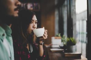 hipster paar op vakantie binnen zitten café koffie drinken foto