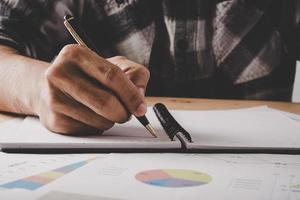 jonge zakenman schrijft in een notitieblok tijdens het werken op kantoor foto