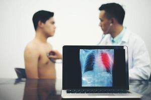 arts met patiënt bij kliniek met x-ray film op laptop foto
