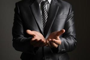 jonge zakenman die copyspace presenteert geïsoleerd op zwarte achtergrond foto
