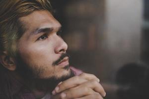 nadenkend jonge hipster man zit in een coffeeshop denken foto